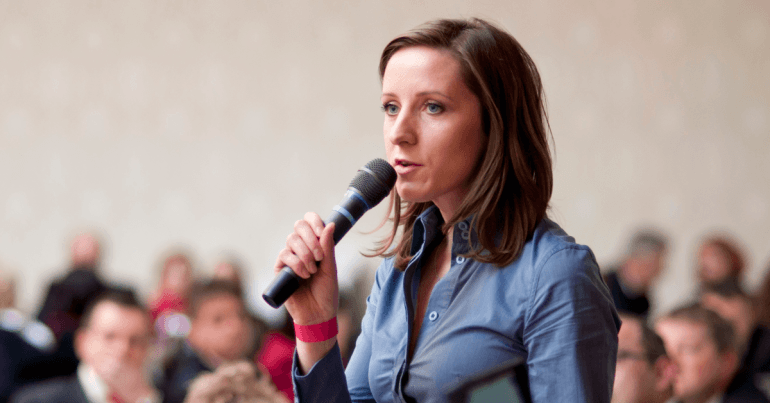 30ish white woman in a blue shirt holding a microphone and speaking