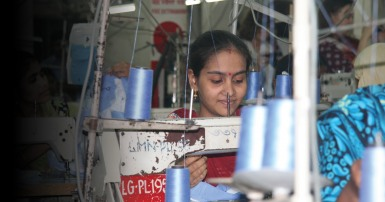 Young woman at a sewing machine in a factory