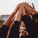 Soft focus image of a small group of women with their arms raised, touching hands