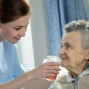 Young woman in blue scrubs standing beside bed holding a cup of orange liquid to the mouth of an elderly woman