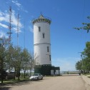 Photo of tall white water tower against a blue sky